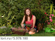 Купить «Прекрасная веселая шатенка подрезает растения в саду», фото № 5978180, снято 20 января 2020 г. (c) BE&W Photo / Фотобанк Лори