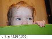 Сероглазая девочка смотрит в сторону из за спинки стула. Стоковое фото, фотограф Елена Стрильчук / Фотобанк Лори