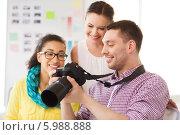 Купить «Фотограф показывает сотрудницам офиса результаты своей работы», фото № 5988888, снято 17 мая 2014 г. (c) Syda Productions / Фотобанк Лори