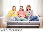 Купить «Три подруги сидят на диване, поджав ноги, и смотрят сериал по телевизору», фото № 5988912, снято 12 апреля 2014 г. (c) Syda Productions / Фотобанк Лори