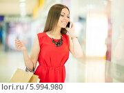 Купить «Красивая девушка с длинными волосами в красном платье делает покупки, держит пакеты и разговаривает по телефону», фото № 5994980, снято 10 июня 2014 г. (c) Вера Франц / Фотобанк Лори