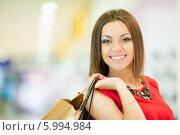 Купить «Красивая девушка с длинными волосами в красном платье делает покупки, держит пакеты», фото № 5994984, снято 10 июня 2014 г. (c) Вера Франц / Фотобанк Лори