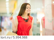 Купить «Красивая девушка с длинными волосами в красном платье делает покупки, держит кредитную карту», фото № 5994988, снято 10 июня 2014 г. (c) Вера Франц / Фотобанк Лори