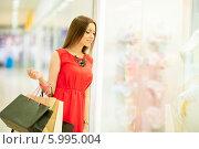 Купить «Красивая девушка с длинными волосами в красном платье делает покупки», фото № 5995004, снято 10 июня 2014 г. (c) Вера Франц / Фотобанк Лори