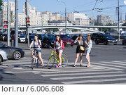 Девушки-велосипедистки стоят на пешеходном переходе в Москве (2014 год). Редакционное фото, фотограф Евгений Самсонов / Фотобанк Лори