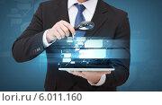 Купить «Бизнесмен с лупой смотрит на экран планшетного компьютера», фото № 6011160, снято 14 ноября 2013 г. (c) Syda Productions / Фотобанк Лори