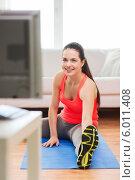 Занятия фитнесом перед телевизором дома. Девушка выполняет упражнения на растяжку. Стоковое фото, фотограф Syda Productions / Фотобанк Лори