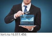 Купить «Бизнесмен рассматривает под лупой экран планшетного комьютера», фото № 6011456, снято 14 ноября 2013 г. (c) Syda Productions / Фотобанк Лори