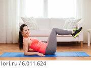 Фитнес дома. Привлекательная девушка выполняет упражнения на коврике в своей квартире. Стоковое фото, фотограф Syda Productions / Фотобанк Лори