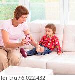 Купить «Мама обувает маленькую дочку, сидящую на диване», фото № 6022432, снято 20 сентября 2018 г. (c) BE&W Photo / Фотобанк Лори