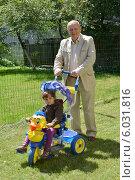 Купить «Дедушка катает внучку на трехколесном велосипеде», фото № 6031816, снято 22 июня 2014 г. (c) Ирина Борсученко / Фотобанк Лори