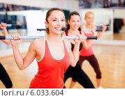 Купить «Группа девушек под руководством тренера занимается с гимнастическими палками в спортивном зале», фото № 6033604, снято 28 сентября 2013 г. (c) Syda Productions / Фотобанк Лори