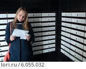 Счастливая женщина читает письмо рядом с почтовыми ящиками. Стоковое фото, фотограф Данил Руденко / Фотобанк Лори