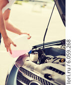 Купить «man filling windscreen water tank», фото № 6059268, снято 5 июля 2013 г. (c) Syda Productions / Фотобанк Лори