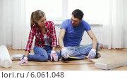 Купить «Smiling couple measuring wood flooring», видеоролик № 6061048, снято 31 января 2014 г. (c) Syda Productions / Фотобанк Лори