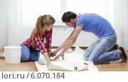 Купить «Smiling couple cutting wallpaper», видеоролик № 6070184, снято 31 января 2014 г. (c) Syda Productions / Фотобанк Лори