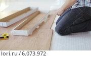 Купить «Close up of male hands measuring wood flooring», видеоролик № 6073972, снято 10 февраля 2014 г. (c) Syda Productions / Фотобанк Лори