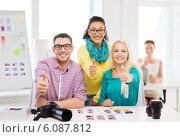 Купить «smiling team with printed photos working in office», фото № 6087812, снято 17 мая 2014 г. (c) Syda Productions / Фотобанк Лори