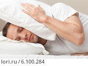 Мужчина закрывает голову подушками, чтобы не слышать шум. Стоковое фото, фотограф EugeneSergeev / Фотобанк Лори
