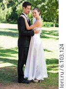 Young newly wed couple embracing in garden. Стоковое фото, агентство Wavebreak Media / Фотобанк Лори