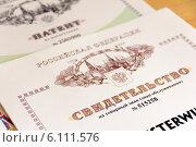 Купить «Свидетельство на товарный знак на фоне патента на изобретение», эксклюзивное фото № 6111576, снято 9 июля 2014 г. (c) Юрий Шурчков / Фотобанк Лори