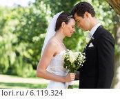 Newly wed couple with head to head in garden. Стоковое фото, агентство Wavebreak Media / Фотобанк Лори