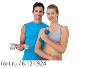 Купить «Portrait of a fit couple exercising with dumbbells», фото № 6121924, снято 10 ноября 2013 г. (c) Wavebreak Media / Фотобанк Лори