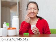 Купить «Happy woman puts cream on face», фото № 6145612, снято 9 декабря 2012 г. (c) Яков Филимонов / Фотобанк Лори
