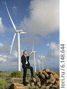 Man using a mobile phone next to wind turbines. Стоковое фото, фотограф Phovoir Images / Фотобанк Лори