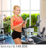 smiling sporty woman with smartphone and earphones. Стоковое фото, фотограф Syda Productions / Фотобанк Лори