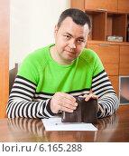Купить «Расстроенный мужчина с пустым бумажником сидит за столом в домашней обстановке», фото № 6165288, снято 21 марта 2019 г. (c) Дарья Филимонова / Фотобанк Лори