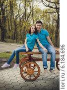 Парень и девушка сидят на деревянной скамье в парке. Стоковое фото, фотограф Юлия Ротанина / Фотобанк Лори