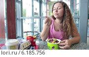 Купить «Молодая женщина с набором из салата, картошки, гамбургера и газированного напитка за столом в ресторане Макдональдс», видеоролик № 6185756, снято 22 июля 2014 г. (c) Кекяляйнен Андрей / Фотобанк Лори