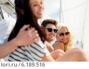 Купить «smiling friends sitting on yacht deck», фото № 6189516, снято 13 июля 2014 г. (c) Syda Productions / Фотобанк Лори