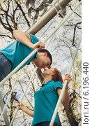 Девушка и парень в одинаковых футболках целуются в парке весной. Стоковое фото, фотограф Юлия Ротанина / Фотобанк Лори