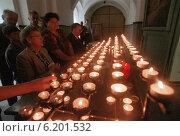 Believers lighting candles in a church, Gora Swietej Anny, Poland (1996 год). Редакционное фото, агентство Caro Photoagency / Фотобанк Лори