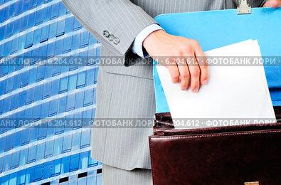 Мужчина кладет бланк договора в портфель на фоне современного здания