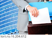 Купить «Мужчина кладет бланк договора в портфель на фоне современного здания», фото № 6204612, снято 7 июня 2018 г. (c) Виталий Радунцев / Фотобанк Лори