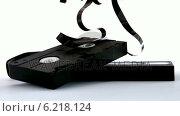 Купить «Broken video tape falling on white background», видеоролик № 6218124, снято 17 января 2019 г. (c) Wavebreak Media / Фотобанк Лори