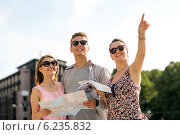 Купить «smiling friends with map and city guide outdoors», фото № 6235832, снято 20 июля 2014 г. (c) Syda Productions / Фотобанк Лори