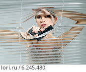 Woman's portrait while looking out the blinds and holding the gun. Стоковое фото, агентство BE&W Photo / Фотобанк Лори