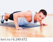 Купить «smiling man doing push-ups in the gym», фото № 6249672, снято 28 сентября 2013 г. (c) Syda Productions / Фотобанк Лори