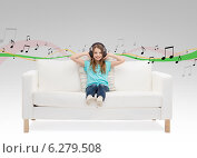 Купить «smiling little girl in headphones sitting on sofa», фото № 6279508, снято 9 апреля 2014 г. (c) Syda Productions / Фотобанк Лори