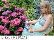 Купить «Молодая беременная женщина-художник пишет акварелью цветы гортензии в саду», фото № 6280212, снято 7 августа 2014 г. (c) Ирина Борсученко / Фотобанк Лори