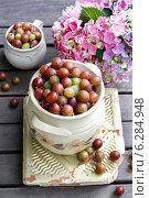 Купить «Jug of gooseberry on wooden table. Summer fruits», фото № 6284948, снято 17 января 2019 г. (c) BE&W Photo / Фотобанк Лори