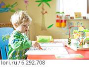 A boy colouring a book. Стоковое фото, агентство BE&W Photo / Фотобанк Лори