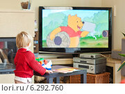 Купить «A child watching tv at home», фото № 6292760, снято 25 июня 2019 г. (c) BE&W Photo / Фотобанк Лори