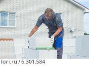 Купить «Рабочий укладывает газосиликатные блоки», фото № 6301584, снято 19 августа 2014 г. (c) Андрей Батурин / Фотобанк Лори