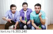 Купить «Happy male friends with beer watching tv at home», видеоролик № 6303240, снято 8 апреля 2014 г. (c) Syda Productions / Фотобанк Лори