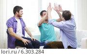 Купить «Smiling male friends giving high five at home», видеоролик № 6303284, снято 8 апреля 2014 г. (c) Syda Productions / Фотобанк Лори